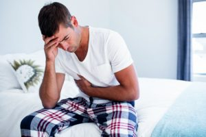 man with stomach pain sitting on bed | leaky gut test | Perpetual Wellbeing