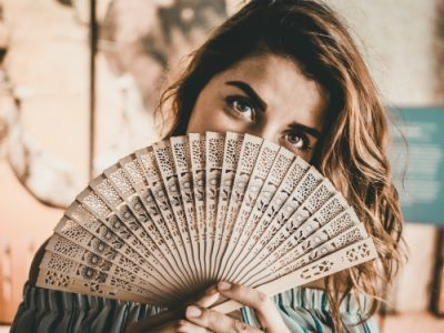 what causes hot flushes | woman with a fan | Perpetual Wellbeing