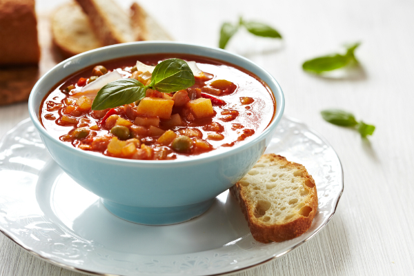 bowl of minestrone soup with a slice of bread