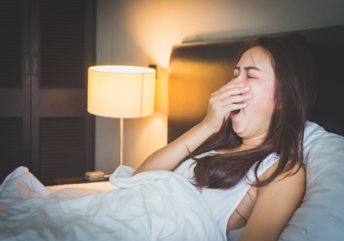 woman yawning in bed at night - what causes insomnia | Perpetual Wellbeing