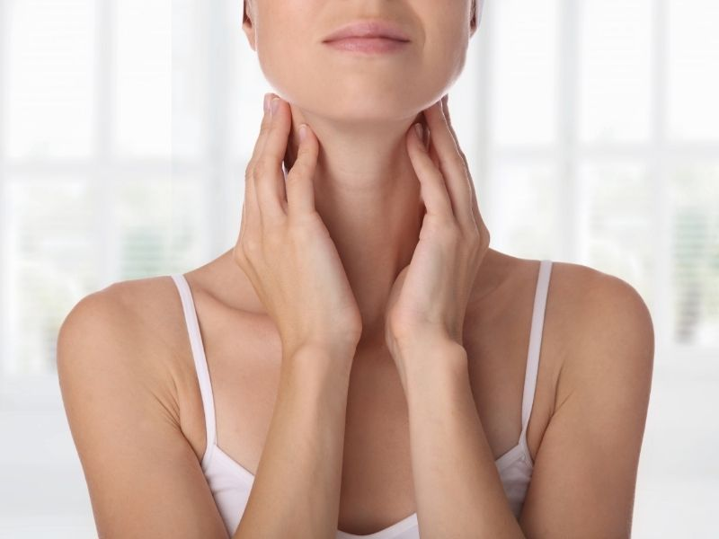 woman touching neck | signs and symptoms of thyroid issues | Perpetual Wellbeing