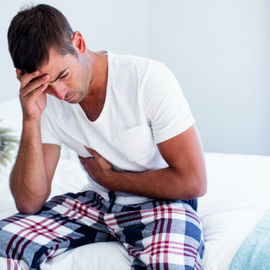 man with stomach pain sitting on bed | Intestinal Permeability | Perpetual Wellbeing