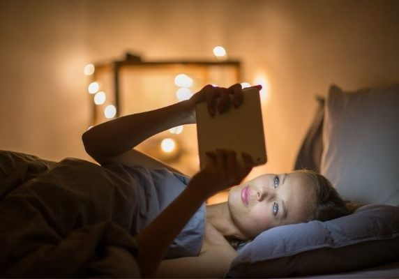 woman using device in bed | why is melatonin important for sleep | Perpetual Wellbeing
