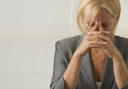 woman with eyes closed showing signs and symptoms of stress | Perpetual Wellbeing
